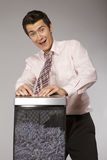 Young caucasian businessman with tie trapped in shredded machine Stock Photos