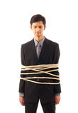 A young Caucasian businessman tied in ropes Stock Image
