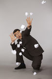 Young caucasian businessman under paper ball attack Stock Image