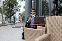 Young caucasian businessman using his laptop in cafe - drinking Royalty Free Stock Image