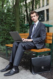 young caucasian businessman using his laptop in park Stock Photo