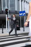 Young caucasian businessman walking on red light Stock Image