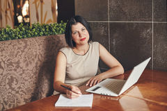 Young caucasian businesswoman with laptop and notebook. Woman in cafe Royalty Free Stock Images