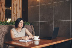 Young caucasian businesswoman with laptop and notebook. Woman in cafe Stock Image
