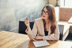 Young caucasian businesswoman with notebook. Woman in glasses in a cafe Stock Photos