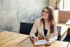Young caucasian businesswoman with notebook. Woman in glasses in a cafe Royalty Free Stock Photos