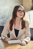 Young caucasian businesswoman with notebook. Woman in glasses in a cafe Royalty Free Stock Images