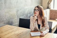 Young caucasian businesswoman with notebook. Woman in glasses in a cafe Royalty Free Stock Photography