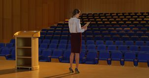 Young Caucasian businesswoman practicing speech in empty auditorium 4k. Rear view of young Caucasian businesswoman practicing speech in empty auditorium.She is stock video footage
