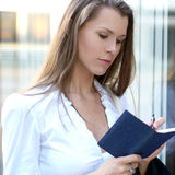 A young Caucasian businesswoman reading a diary Stock Photo