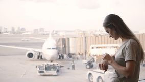 Young Caucasian businesswoman standing at airport terminal lounge window using smart watch, looking at airplanes. Female traveler using mobile office app stock video footage