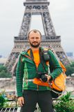 A young Caucasian Caucasian man with an orange backpack and a photo camera in his hands is standing in France, paris against the b stock images