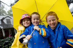 Young caucasian children playing in the rain. With yellow umbrella and blue raincoats Royalty Free Stock Photos