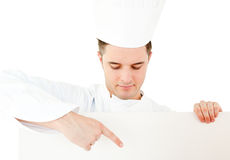 Young caucasian cook showing on a white placard Royalty Free Stock Images
