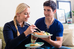 Young Caucasian couple eating Asian traditional food at home. Young Caucasian couple eating Asian traditional food with chopsticks while sitting on the couch at stock photo