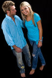 Young Caucasian Couple Embracing. Young Caucasian Couple in blue shirts and jeans embracing. Shot on a black background Stock Image