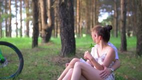 Young caucasian couple have a rest on the grass after cycling through the forest stock footage