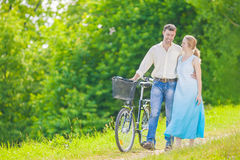 Young Caucasian Couple Having a stroll in Park with Bike Stock Photography