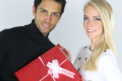 Young Caucasian couple holding a Christmas present Royalty Free Stock Image