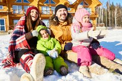 United family on winter weekend. Young Caucasian couple with little kids sitting in snow outdoors, enjoying bright sun and smiling happily Stock Image