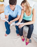 Young caucasian couple looking at bills on sofa royalty free stock image