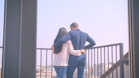 Young caucasian couple in love embraces on balcony and enjoying magnificent city view. Young caucasian couple in love embraces on balcony and enjoying stock video footage