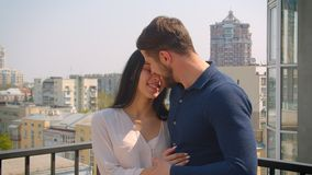 Young caucasian couple in love hugging and kissing tenderly on terrace enjoying city view. Young caucasian couple in love hugging and kissing tenderly on stock video footage