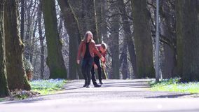 Young man and woman wearing light-brown jacket joyfully walk in empty park. stock video