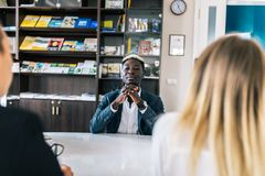 Young caucasian couple at meeting with african american man in formal wear talking at table in modern office royalty free stock image