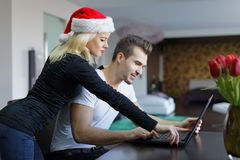 Young caucasian couple online shopping for Christmas by laptop a Stock Image