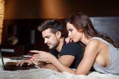 Young couple online shopping by laptop on bed Royalty Free Stock Photo