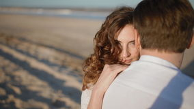 Young caucasian couple on the seaside. Young european white couple sit on the beach.Woman stroke on the shoulder of her partner and time after tome look at the stock video footage