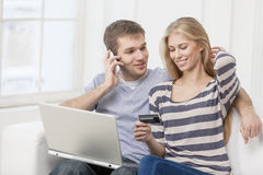 Young caucasian couple sitting on couch Royalty Free Stock Photos