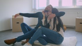 Young caucasian couple are sitting on floor of new house near window and cardboxes dreaming about life in new home. Young caucasian couple are sitting on floor stock video