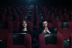 Young caucasian couple sitting in movie theater. Upset brunette girl watching film, while her boyfriend messaging using smartphone Stock Photography