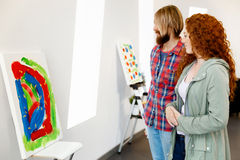 Young caucasian couple standing in a gallery and contemplating artwork. Young caucasian couple standing in a gallery and contemplating abstract artwork Stock Photos