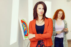 Young caucasian couple standing in a gallery and contemplating artwork. Two young women in a gallery and contemplating abstract artwork Royalty Free Stock Image