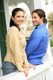 Young Caucasian Couple Talking On Patio. Happy and smiling couple enjoying outdoor in front of their house stock images
