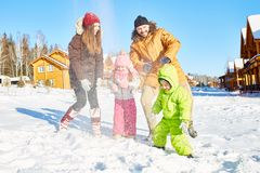 Happy family on winter holidays. Young Caucasian couple and their little kids playing with snow and smiling happily on beautiful winter afternoon out of town Stock Photo