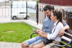 Young Caucasian Couple Travelling Across the City. Checking Route. Using City Map Outdoors. Horizontal Image royalty free stock image