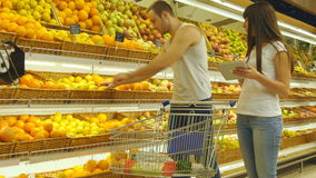 Young caucasian couple walking in a supermarket with a market trolley and choosing fresh apples. Man is putting fruits. Into the shop basket. Woman is using stock video footage