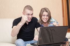 Young Caucasian couple winning lottery or doing bet per win with on-line gamble service. S Stock Photography