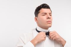 Young Caucasian dark hair man tie up. Cool young Caucasian dark hair man tie up his bow isolated on white Royalty Free Stock Photos