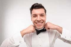 Young Caucasian dark hair man tie up. Smiling young Caucasian dark hair man tie up his bow isolated on white Stock Images
