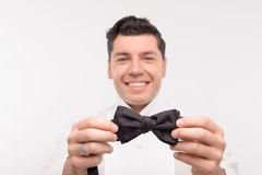 Young Caucasian dark hair man tie up. Young caucasian dark hair man smiling takes his bow tie in hands Royalty Free Stock Photos