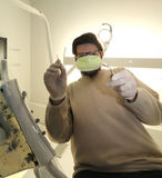 Young caucasian dentist with green health mask and tooth care eq Stock Photography