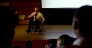 Young Caucasian disabled businessman speaking in business seminar in auditorium 4k. Front view of handsome young Caucasian disabled businessman speaking in stock footage