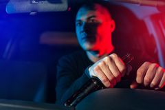 Young caucasian drunk man in auto chased by police. Driver with alcohol bottle in car Royalty Free Stock Image