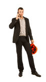 Young Caucasian Engineer Calling Through Phone. Young Caucasian Male Engineer Calling Through Mobile Phone while Holding Orange Helmet. Isolated on White Stock Photo