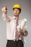 Young caucasian engineer with plans pointing finger away Royalty Free Stock Photo